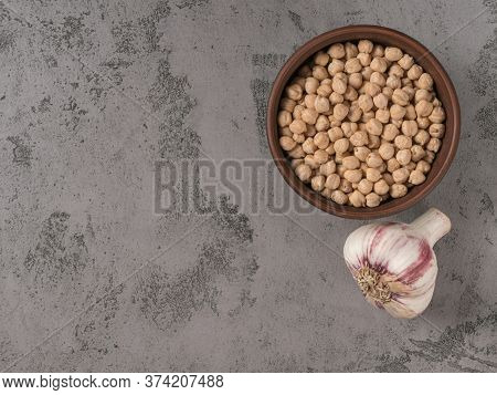 Chickpeas And Garlic Closeup. The Gray Background.