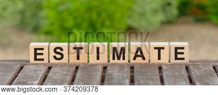 Word Estimate Is Made Of Wooden Building Blocks Lying On The Table And On A Light Green Background.