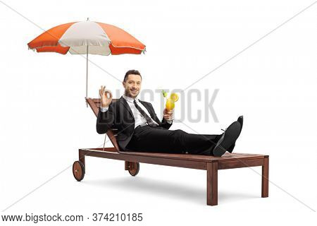 Businessman on a sunbed under umbrella holding a cocktail and gesturing an ok sign isolated on white background
