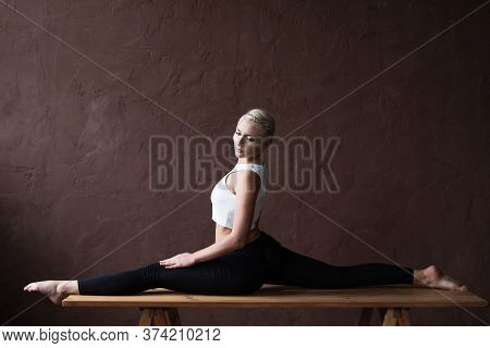 Young Beautiful Athletic Girl In Leggings And Top Sat On A Twine