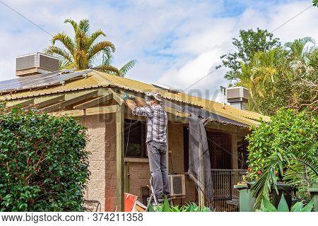 Townsville, Queensland, Australia - June 2020: Man Standing On Trestles Sanding Roof Rafters Of Resi