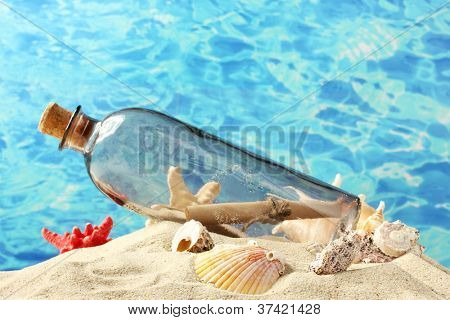 Glass bottle with note inside on sand, on blue sea background