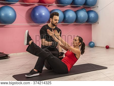 Young Woman Helped By Her Coach Is Doing Exercises In A Gym.