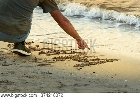 A Man Crouched Down Writing With His Finger A Message On The Sand Next To The Sea At Sunset, Rhodes,