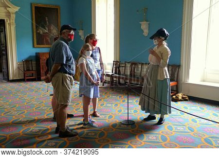 Williamsburg, Virginia, U.s.a - June 30, 2020 - A Lady In Colonial Costume Assisting Visitors During