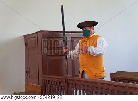Williamsburg, Virginia, U.s.a - June 30, 2020 - A Man In Colonial Costume Inside A Court House Assis