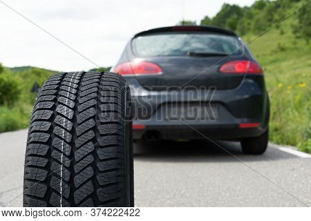 Picture Of Black Car's Brand New Tyre On The Road On A Summer Day