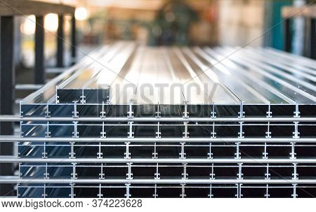 Aluminiun Profiles Placed In A Row Inside An Aluminium Profile Factory.