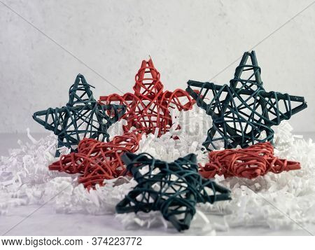 Red And Blue Wooden Stars Set On A Bed Of White Paper Shreds With A Plaster Background For 4th Of Ju