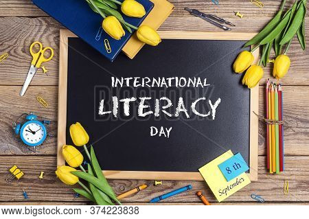 International Literacy Day Background With A Chalkboard, School Supplies And Tulip Flowers On A Rust