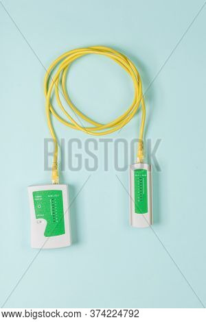 Lan Tester And Yellow Cable On Blue Background. Connection To The Internet.