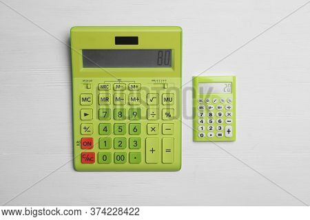 Different Calculators With Numbers 80 And 20 On White Wooden Background, Flat Lay. Pareto Principle