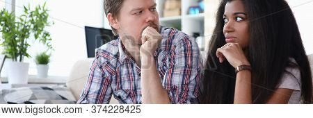 Couple Sitting Sofa At Home Looking At Each Other. Tensions Between Spouses, Unwillingness To Compro