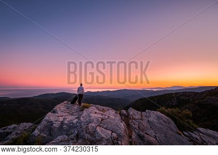 A Man And His Border Collie Dog Enjoy The View Of The Coastline And The Mediterranean Sea At Sunrise