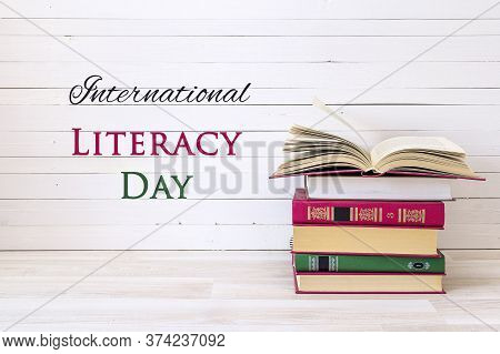 International Literacy Day Concept With Stack Of Books With Open Book On White Wooden Table.