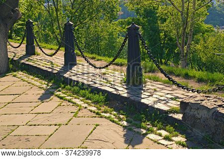 The Alley Is Fenced By A Chain Fence From The Precipice. A Chain Fence Casts A Shadow To The Cobbles