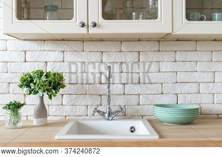 Front View Of Modern Kitchen At Home With White Interior, Sink And Water Tap, Green Plants And Clean