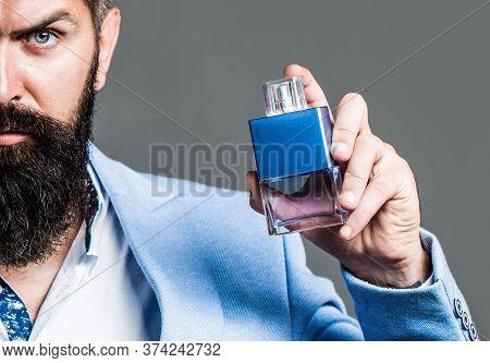 Bearded Man Holding Up Bottle Of Perfume. Man Perfume, Fragrance. Masculine Perfume. Male Fragrance
