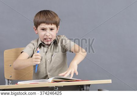 A Primary School Student Is Doing Homework. The Child At The Desk With The Textbook Is Angry. The Bo