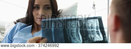 Patient Lying On Bed Looking At Doctor With X-ray. Emergency Medical Care. Comprehensive Program For