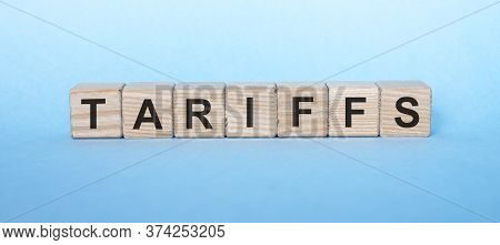 Tariffs Word Written With Wooden Cubes On Blue Background