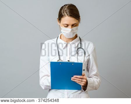Young Woman Physician With Stethoscope Prescribing Treatment To Patient. Female Doctor With Pen Writ
