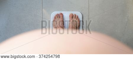 Obese Man Standing Barefoot On A Bathroom Scale - View From Above A Prominent Belly