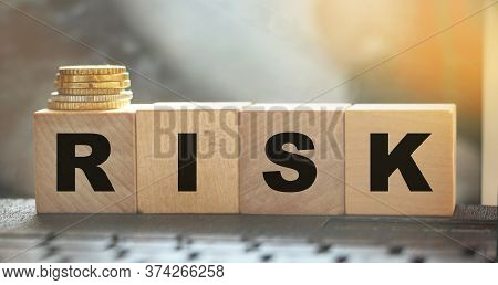 Risk Word On Wooden Blocks Arranged Behind Computer Keyboard And Stack Of Coins. Risky Investment Bu