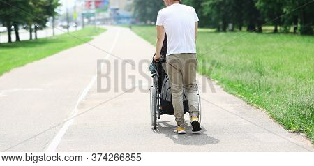Close-up Of Man In White Shirt Accompany Woman In Wheelchair. Person Spending Time With Friend. Walk