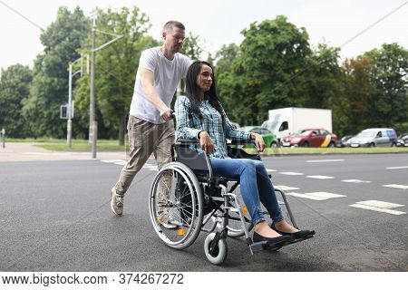 Portrait Of Couple Walking On City Street. Charming Woman Sitting In Wheelchair. Caring Man Accompan