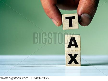 The Hand Puts The Cube Block With The Inscription Tax. Tax Symbol.