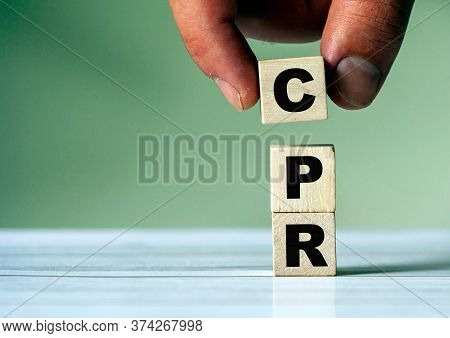 The Hand Puts The Cube Block With The Inscription Cpr. Word Symbol Cpr.
