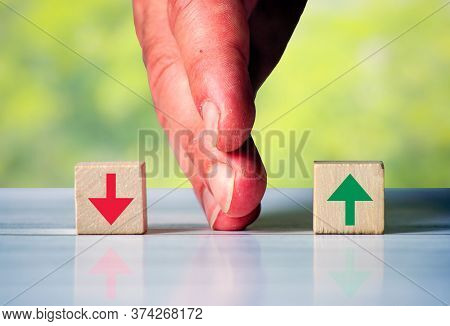 The Hand Separates Two Wooden Blocki With Red Arrow Down And Green Arrow Up. Symbol For The Differen