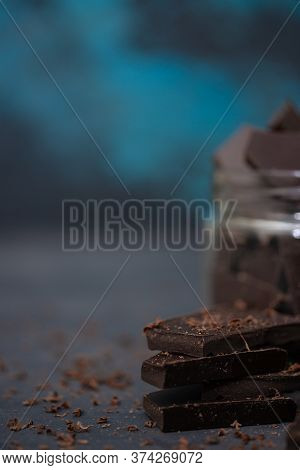 Crushed Dark Chocolate Pieces And Chips On Blurred Dark And Blue Background.