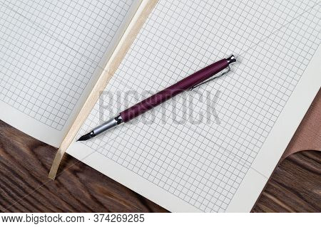 A Part Of Open Daily Planner On Wooden Background With Purple Fountain Pen. Copyspace Template And B