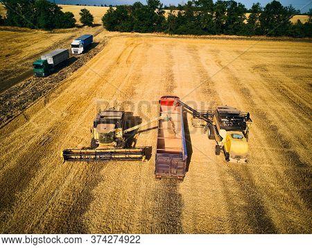 Aerial Drone View. Overloading Grain From Combine Harvesters Into Grain Truck In Field. Harvester Un