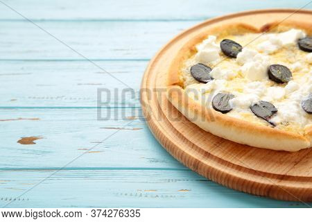 Four Cheese Pizza, Quattro Fromaggi On Cutting Board On Blue Background. Top View