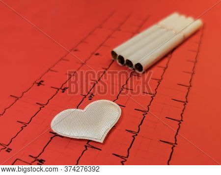 A White Heart On A Background Of Cigarettes Lies On A Red Printout Of The Results Of A Cardiogram. S
