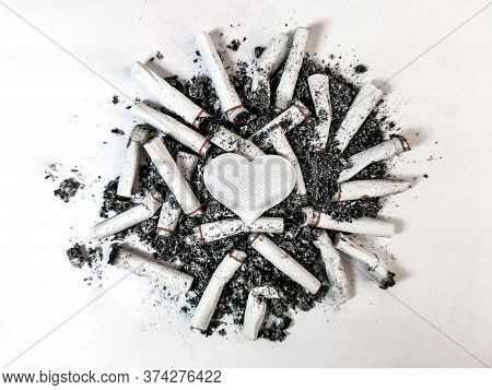 Close-up Of A White Heart Lies In The Center Of A Pile Of Cigarette Butts And Ash On A White Backgro