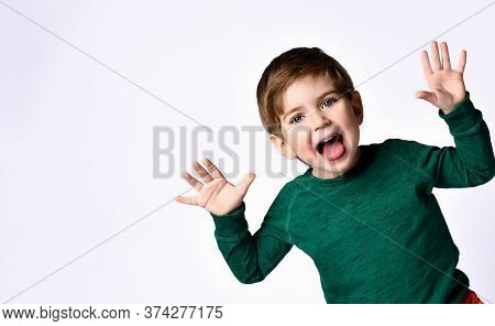 Cute Brunette Kid Dressed In Green Jumper. He Raised His Hands Up, Opened Mouth And Looking Overjoye