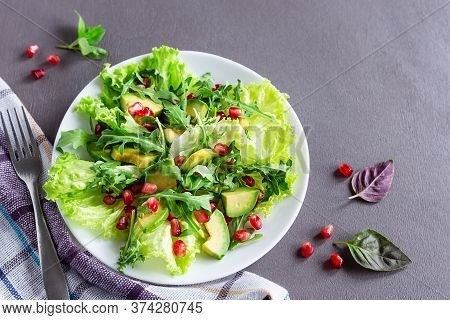 Avocado And Pomegranate Salad On A White Plate On A Gray Background. Healthy Food