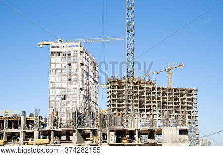 Tower Crane Lifting Concrete Bucket For Pouring Concrete During Construction New Residential Buildin