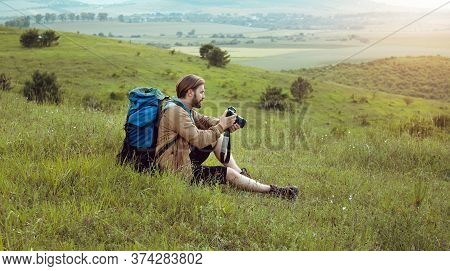 Portrait Of Man With Backpack Sitting On Hill Looking Through Recent Shots On Dslr Camera, Side View