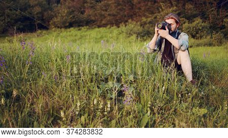 Male Photographer Sitting In Greenery Taking Pictures Using Dslr Camera, Full Length