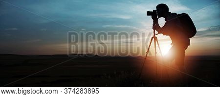 Side Silhouette Of Photographer Taking Pictures Using Dslr Camera And Tripod On Sunset Or Sunrise