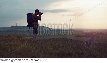 Backpacker Taking Landscape Photos Using Dslr Camera Standing On Hill, Active Lifestyle Concept