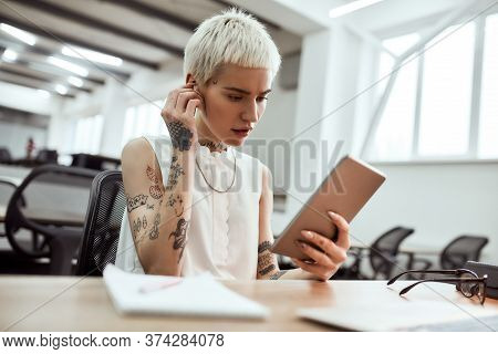 Young Blonde Tattooed Business Woman Putting On Wireless Earphones And Using Her Touchpad While Sitt
