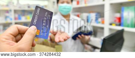 Man Paying For Medicaments With Credit Card In Pharmacy Drugstore.banner Side