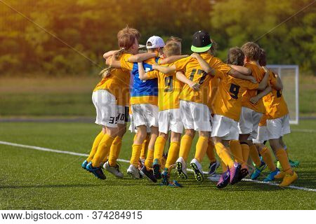 Group Of Young Soccer Players Celebrate A Goal And Winning In A Game. Happy Kids Jumping In A Circle
