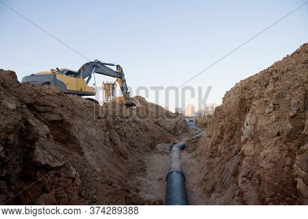 Excavator At Work Trenching At A Construction Site. Trench For Laying External Sewer Pipes. Sewage D